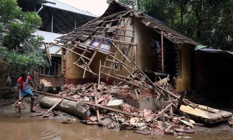 A man removes debris from a collapsed house after floods in Paravur in Kerala Reuters photo